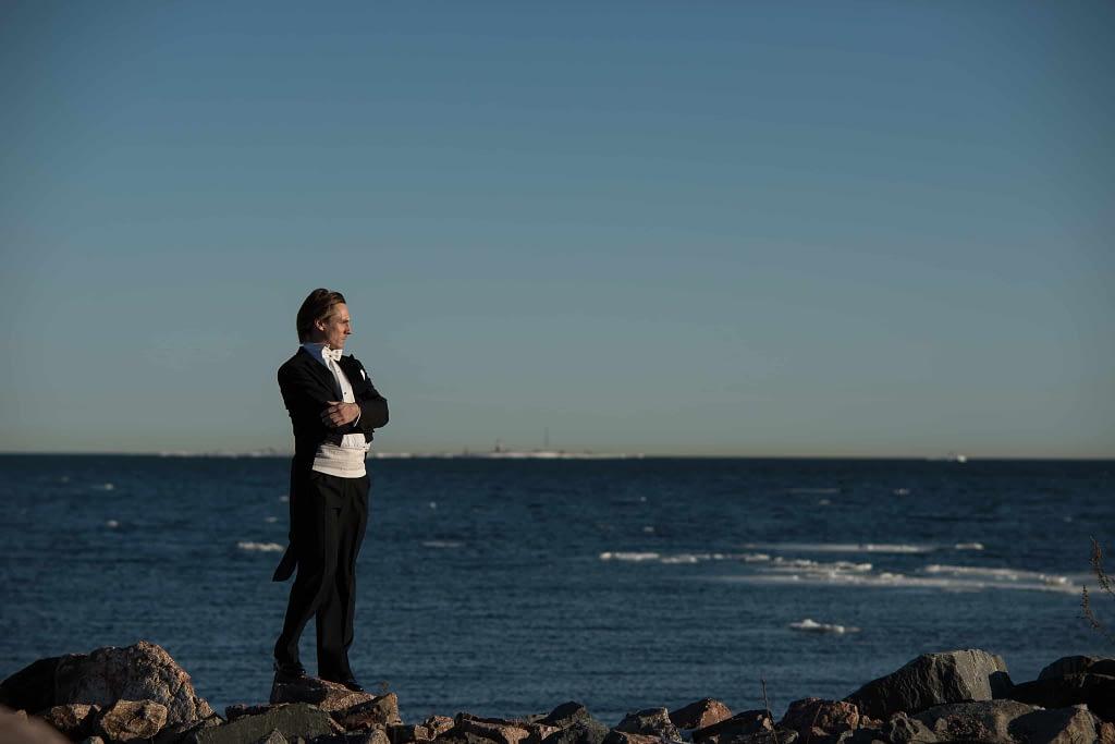 Kapellimestari Teemu Hämäläinen seisoo meren rannalla